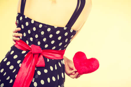 love proof: Valentine day gift, proof of love, romantic present concept. Woman in retro polka dot dress holding small furry red heart Stock Photo