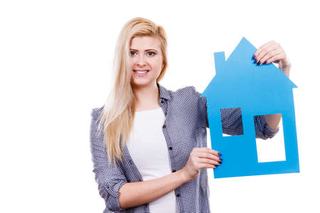 stabilization: Dream about stabilization and family. Blonde girl holding blue paper house model cutout. New flat apartment. Isolated on white