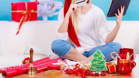 christmas spending: Online shopping, buying Christmas gifts on Internet concept. Woman in Santa hat sitting on sofa holding tablet and credit card, browsing net.