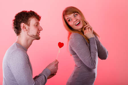 confessing: Romance symbolism valentines concept. Man giving heart to his girl. Young male proffesing love to woman, by giving her heart. Stock Photo