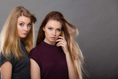 charmingly: Family relationships, friendship concept. Two beautiful women sisters, blonde and brunette with windblown hair posing charmingly. Studio shot on dark grey background Stock Photo