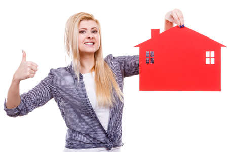 Ownership property real estate concept. Blonde girl holding red paper house symbol making thumb up. New flat apartment. Isolated on white