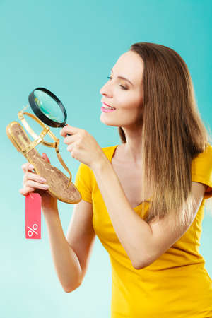Good shopping summer sale concept. Fashionable woman choosing shoes searching through magnifying glass, discount red label with percent sign in hand