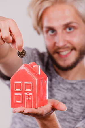 household money: Household savings and finances, economy concept. Man putting money coin into piggy bank in shape of house, studio shot on grey background