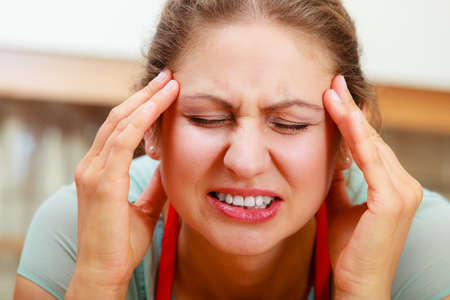 Mature woman suffering from headache migraine pain. Stressed female in kitchen. Stock Photo