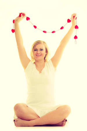 Charity and help. Young blonde woman encourage to helping people and being volunteer. Lovely female with little small red hearts. Stock Photo