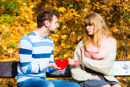 confessing: Confessing love and affection with romantic gesture. Rejection and disapproval. Negative reaction. Pair sit on bench in park man hold plush heart showing his emotions girl refuse. Stock Photo