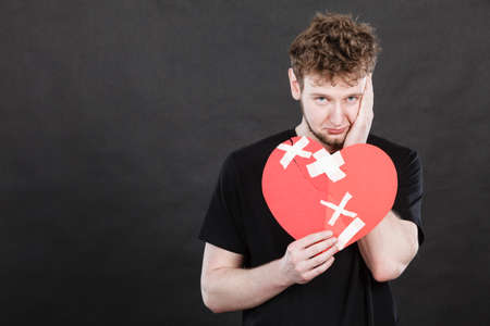 heart very: Bad relationships, breaking up, sadness emotions concept. Very sad young man holding broken heart made of paper.