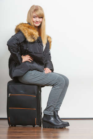 gorgeous girl: Happy young woman in warm jacket with suitcase. Gorgeous blonde tourist travel girl. Tourism. Stock Photo