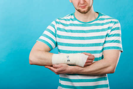 luxacion: Fractures and dislocations concept. Man with hand in bandage. Helpful medication for painful palm arm of young guy.