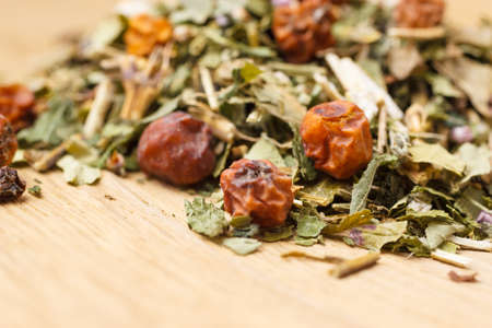 rowanberry: Pile of assorted natural medical dried herb leaves and fruits on wooden surface. Herbaceous plant.