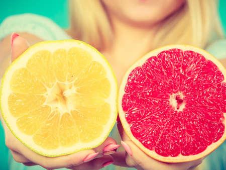 Mitades de cítricos de pomelo amarillo y rojo en las manos Primer femenino. dietista recomienda mujer nutrición dieta saludable.