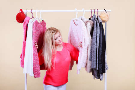 Woman standing in wardrobe with winter clothes, can not decide what to wear. Picking winter clothing concept. Stock Photo