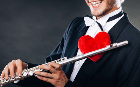 love blow: Valentines day love melody concept. Flute music playing male flutist musician performer. Young elegant stylish guy with instrument and red heart Stock Photo