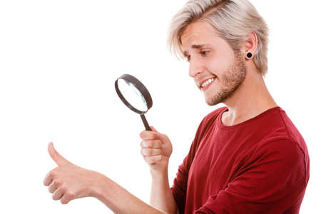 Narcissist, self absorption concept. Male holding magnifying glass looking at hands fingers nails obsessing about cleanliness, isolated on white