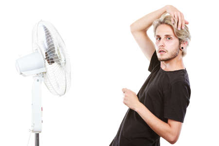 Air conditioning, heat, artistic concept. Young man in front of cooling fan, artistic way fighting with wind holding his hair, studio shot isolated.