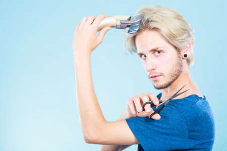 haircutting: Hairdo changing hairstyle concept. Cool male hairstylist making self trendy haircut, fashion blonde metrosexual model going to shave his long hair, using shaver and scissors