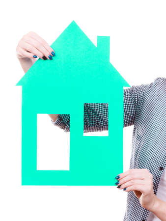 Ownership property concept.. Human hands holding green paper house model cutout. New flat apartment. Isolated on white Stock Photo