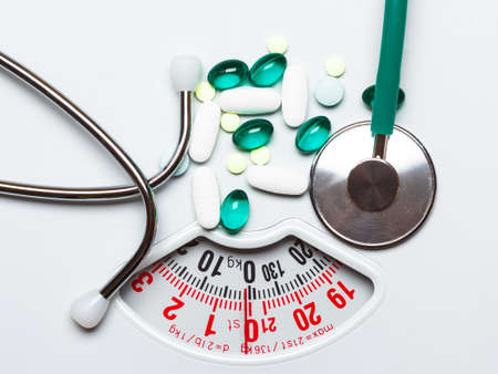 Healthy eating, medicine, health care, food supplements and weight loss concept. Pills with stethoscope on white scales