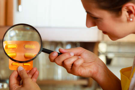 Mature woman female inspecting testing pills tablets food with magnifying glass.