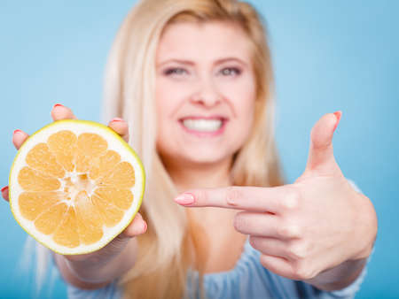 Woman smiling girl holding half of green yellow grapefruit citrus fruit in hand, pointing with finger, recommending healthy eating, on blue. Dieting losing weight concept.