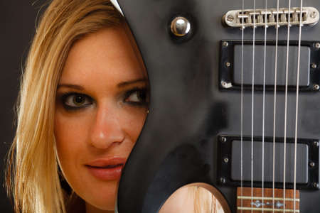 instrumentalist: Music, singing concept. Blonde musically talented woman holding electric guitar on black background