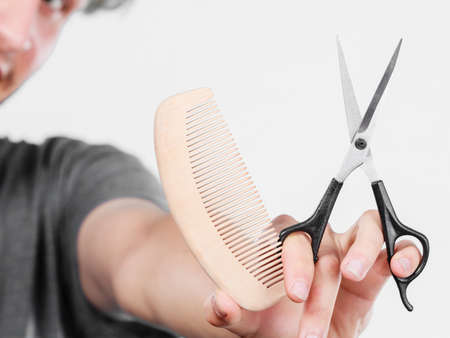 barber scissors: Style and fashion. Male hand of hairstylist barber holds scissors and wooden comb, creating hairdo coiffure