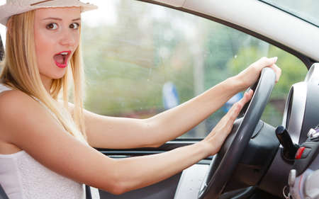 honking: Transportation and vehicle concept. Woman driving car with hand on horn button, female driver honking in traffic