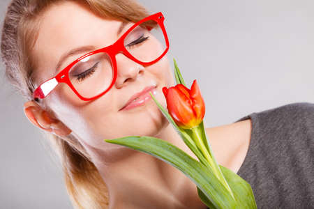 Beauty feminine casual leisure concept. Passionate lady in glasses. Young blonde girl smelling holding red tulip flower tenderly. Stock Photo