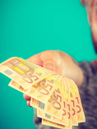Riches, finances concept. Man holding money in 50 euro bills, studio shot on blue background