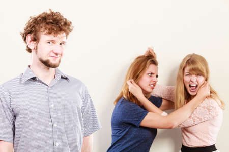wooing: Aggressive mad women fighting over man. Jealous girls wooing guy. Violence.