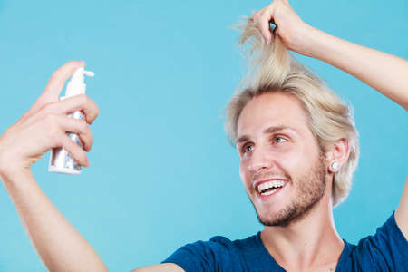 Hairdo haircare and makes hairstyle concept. Handsome young guy, fashion blonde metrosexual model applying spray cosmetic to his hair Stock Photo