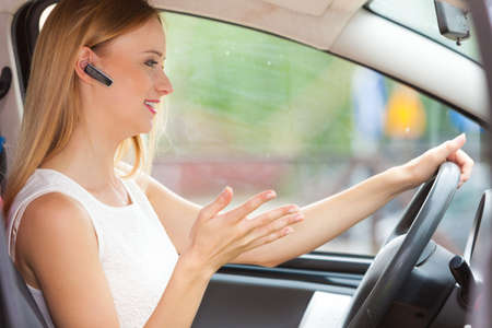 Transport and safety concept. Young blonde woman driving car using her mobile phone and headset, side view Stock Photo