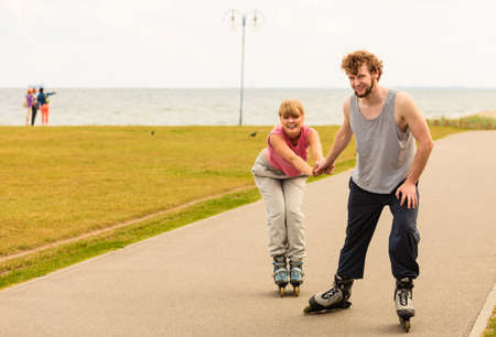 persuade: Active holidays, exercises, relationship concept. Young man dressed in sports clothes putting his girlfriend up to do rollerblading while holding her hand on promenade