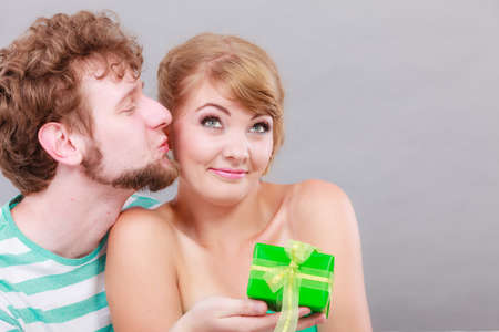 Couple sitting on couch at home. Young man giving woman gift box
