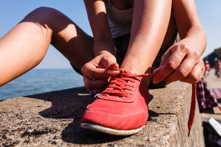 shoelace: Outdoor relax holidays nature concept. Young girl tying shoelace. Lady sunbathing on coast making a knot.