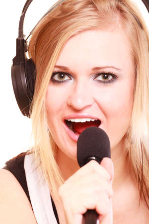 musically: Music, passion concept. Studio shot of blonde young woman singing to microphone and wearing big headphones on her head, isolated portrait