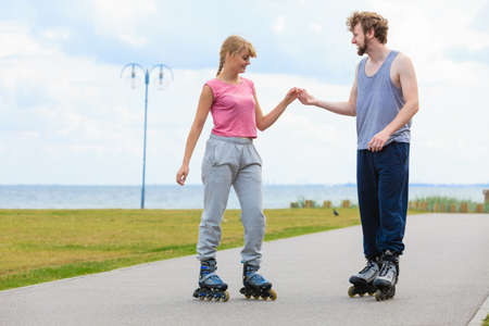 Active holidays, exercises, relationship concept. Young woman and man dressed up in sporty way, holding their hands while rollerblading together on promenade.
