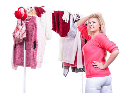 messy clothes: Young woman indecision in wardrobe home closet, teen blonde girl choosing her warm fashion outfit on clothing rack. Picking winter autumn clothes, shopping concept. Stock Photo