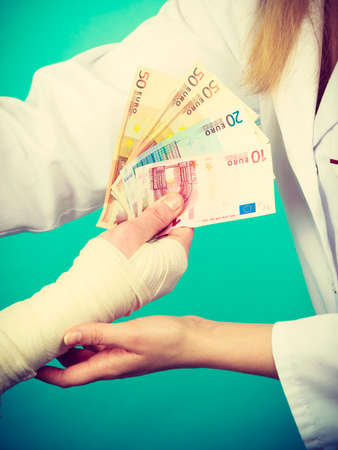 Corruption in healthcare industry. Female doctor bandaging male hand. Man giving money to woman. Bribery in medicine. Stock Photo