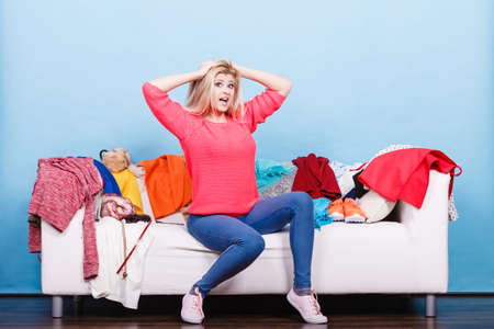 untidy: Clothing dilemmas concept. Woman does not know what to wear sitting on messy couch with piles of clothes. Stock Photo