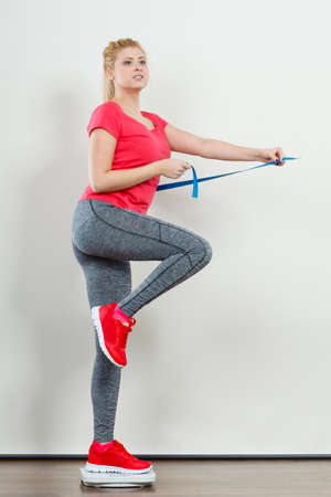 Healthy fit life style, controling body concept. Woman wearing sportswear, leggings and trainers standing on weight machine holding measuring tape. Stock Photo