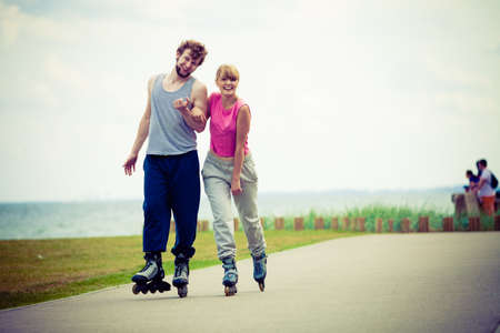 roller blade: Active holidays, exercises, relationship concept. Young woman and man dressed up in sporty way, holding their hands while rollerblading together on promenade.