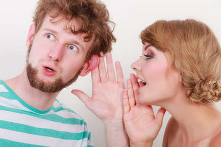 Closeup woman telling an astonished surprised man some secrets, couple talking Stock Photo