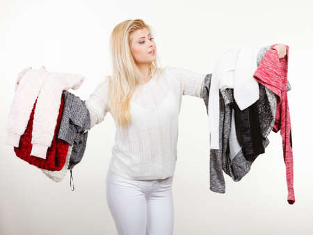 messy clothes: Fashion, clothes dilemmas concept. Woman holding big pile of warm winter clothing, cant decide what to wear, on white grey Stock Photo