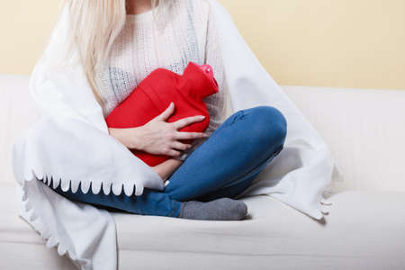 Painful periods and menstrual cramp problems concept. Woman having stomach cramps sitting on cofa feeling very unwell holding hot water bottle to feel some relief