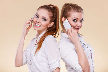 Technology and communication. Lovely teen girls using mobile phones talking, Human emotion, reaction and relationship.