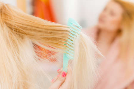 Woman wearing dressing gown brushing her long blonde hair, morning beauty routine. Haircare and hairstyling concept. Stock Photo