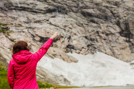 Travel concept. Tourist woman looking and pointing with finger at beautiful mountains landscape in Norway Stock Photo
