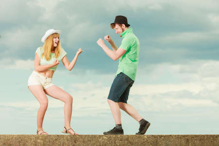 lovers quarrel: Relationship concept. Woman and man young couple in love playing fighting, angry fury girlfriend screaming outdoor on sky background